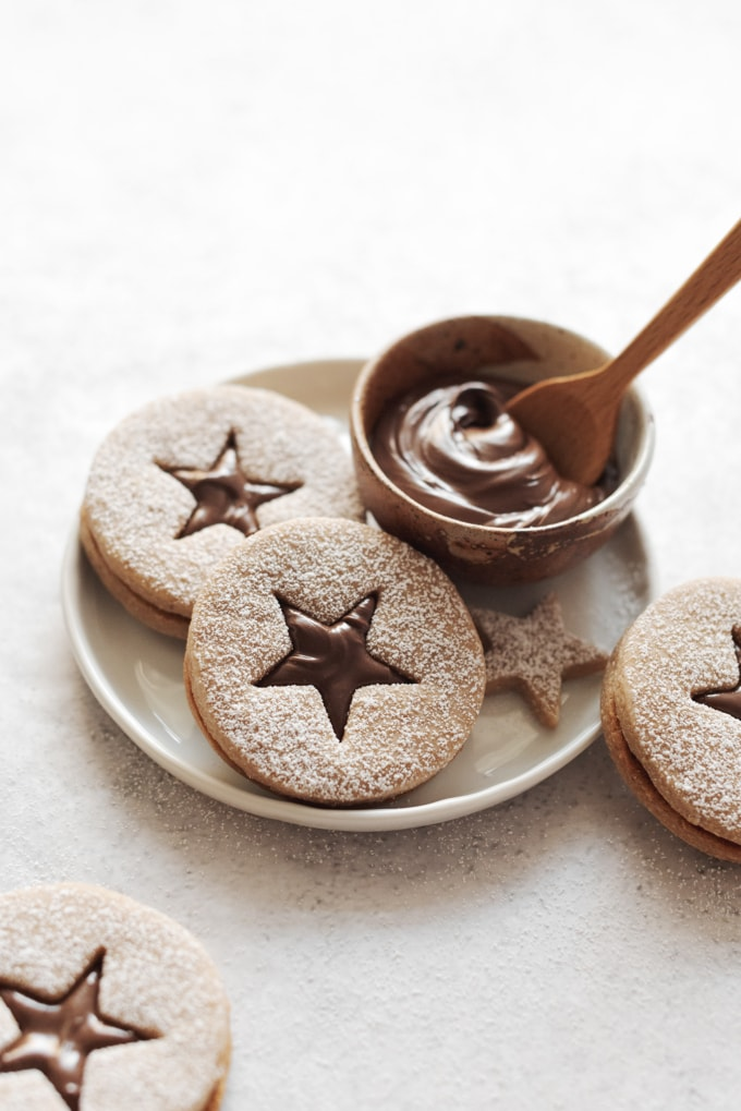 Hazelnut linzer cookies on plate with bowl of Nutella