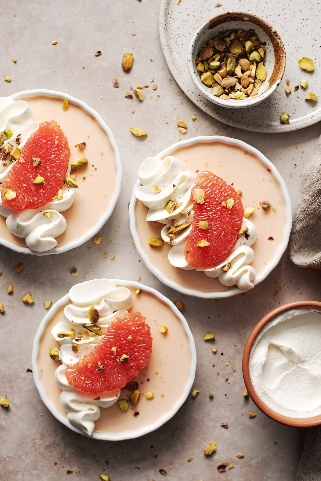 Three panna cottas with whipped cream and grapefruit slices