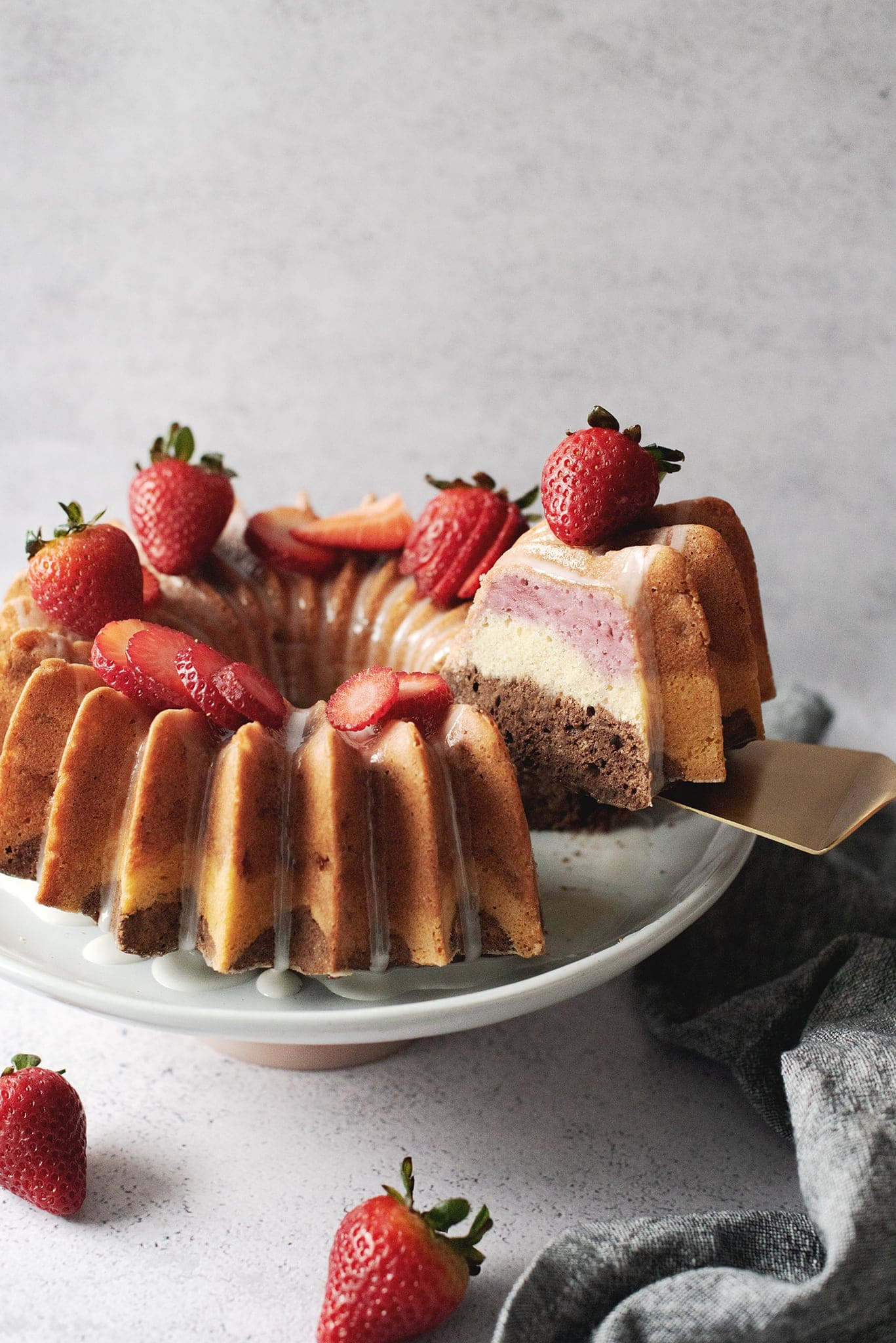 Lifting a slice of neapolitan bundt cake to show layers