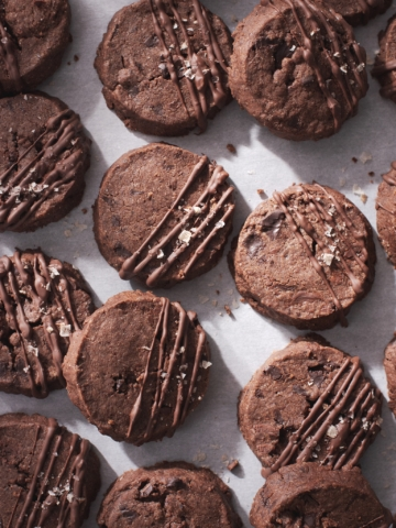 Many chocolate sablé cookies on scattered on baking sheet