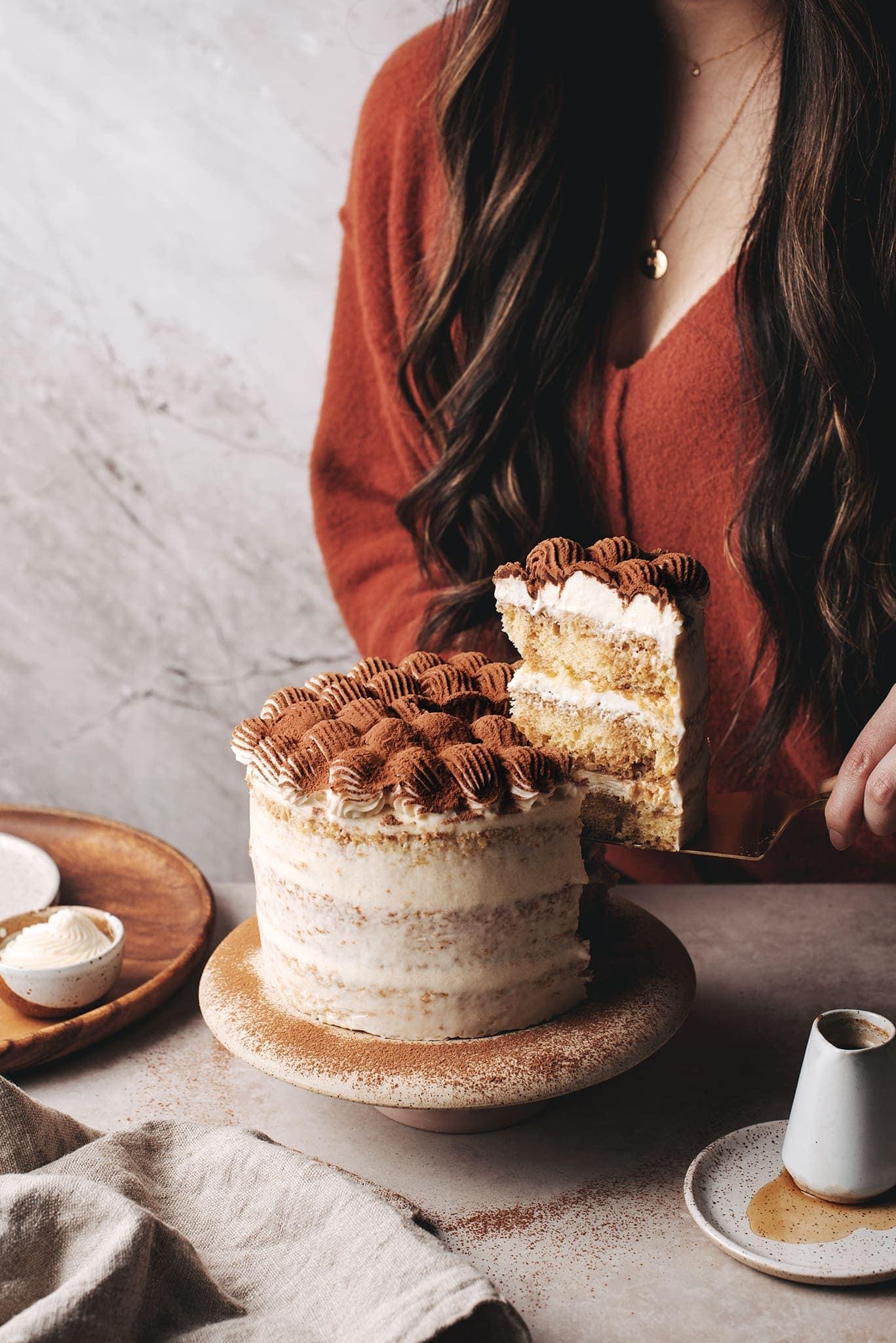 Lifting a slice of tiramisu layer cake with serving knife