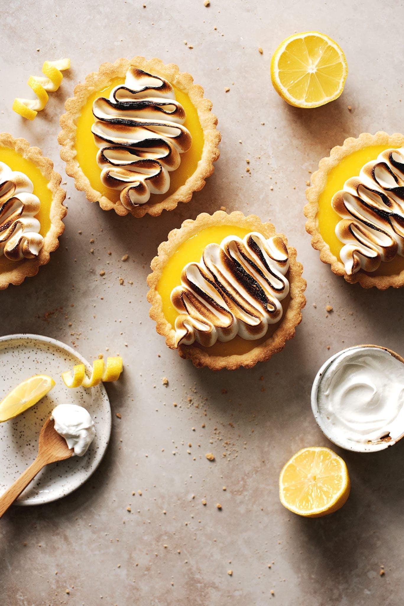 Mini lemon meringue tarts on brown surface