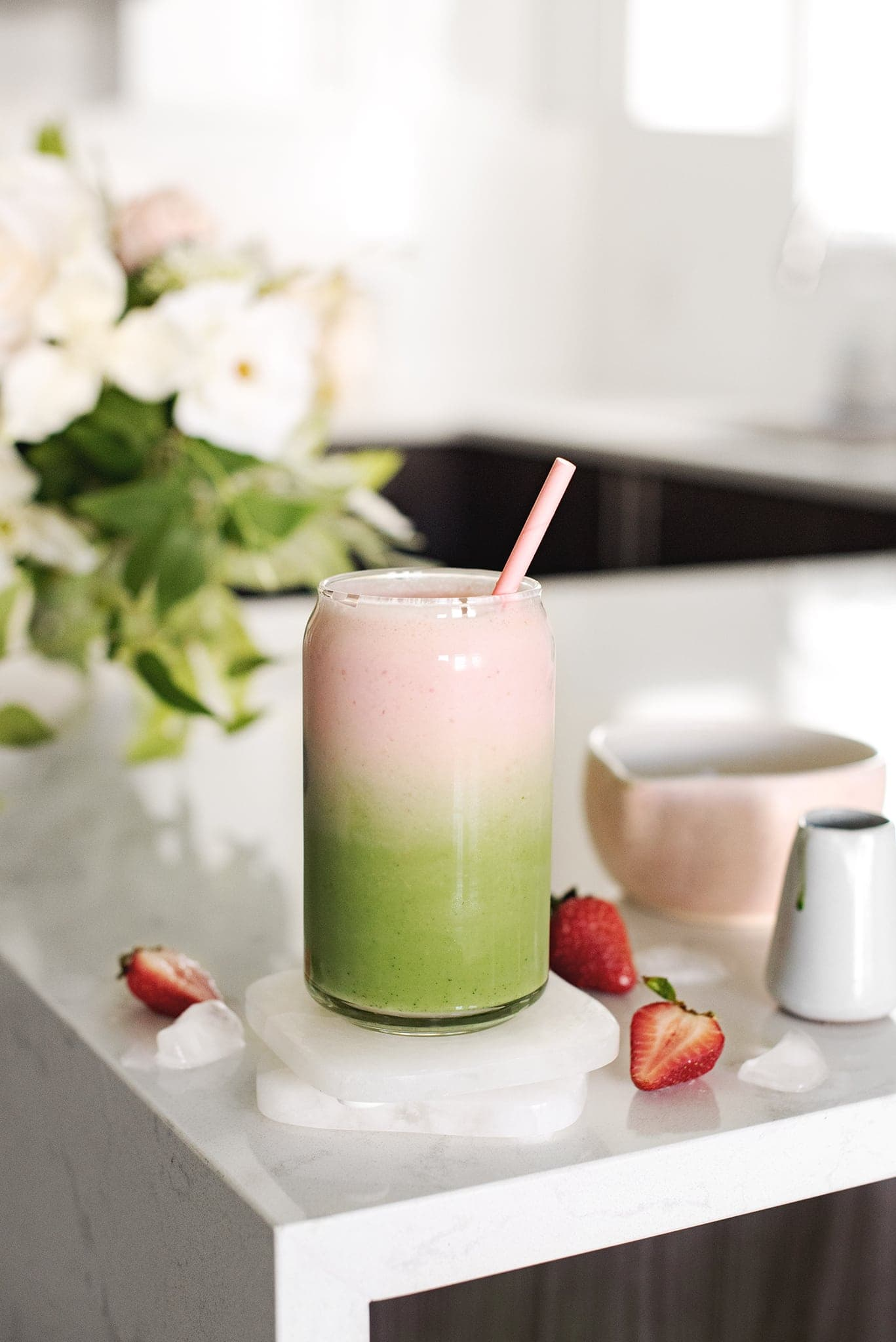 Strawberry matcha latte with green and pink layers in a glass