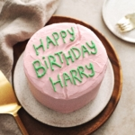Pink cake with 'Happy Birthday Harry' written in green icing