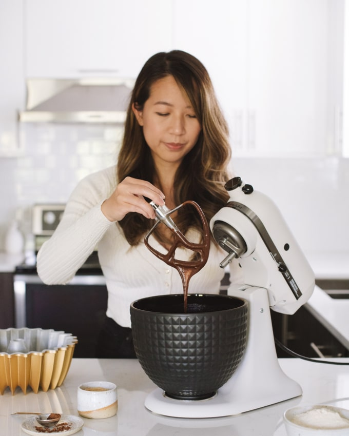 girl holding paddle of stand mixer with batter dripping off