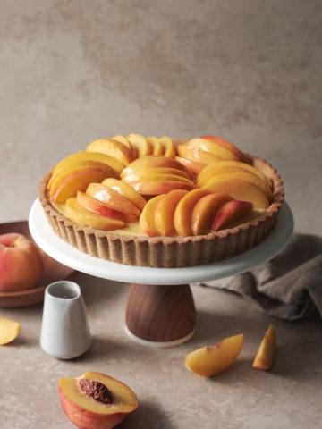 Peach custard tart on a cake stand