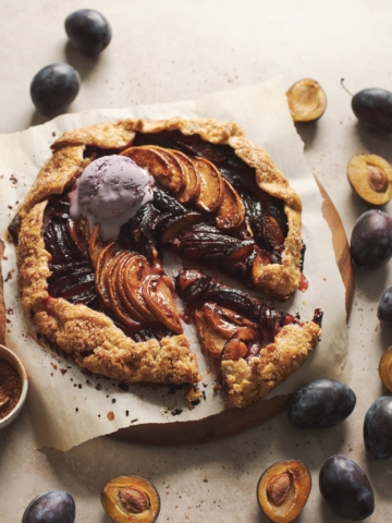 Glossy peach plum galette with a scoop of melting ice cream